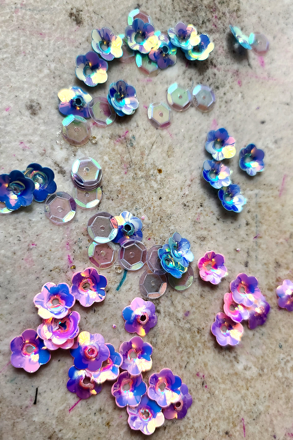 Small piles of various colours and sizes of sequins, on a grey work surface.