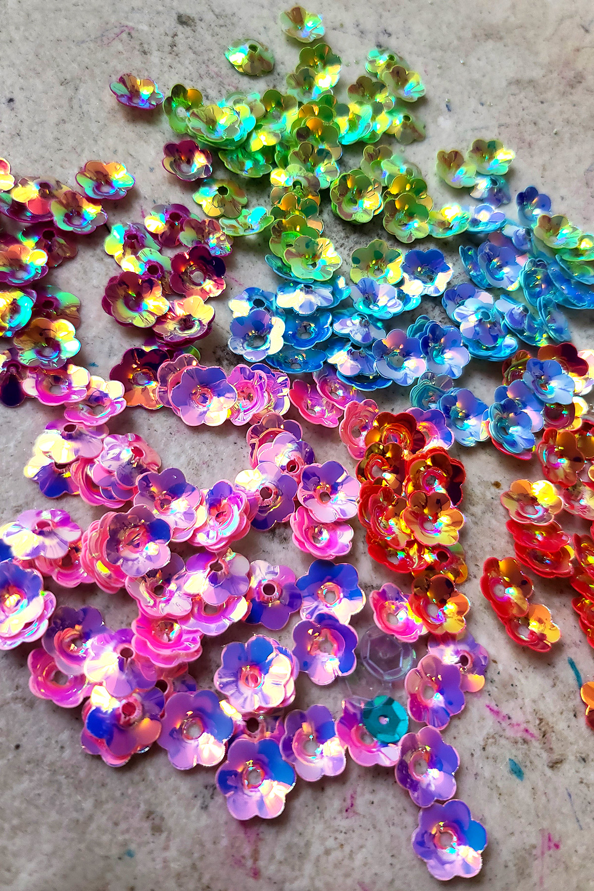 Several piles of iridescent, flower-shaped sequins in pink, orange, blue, green, and purple.