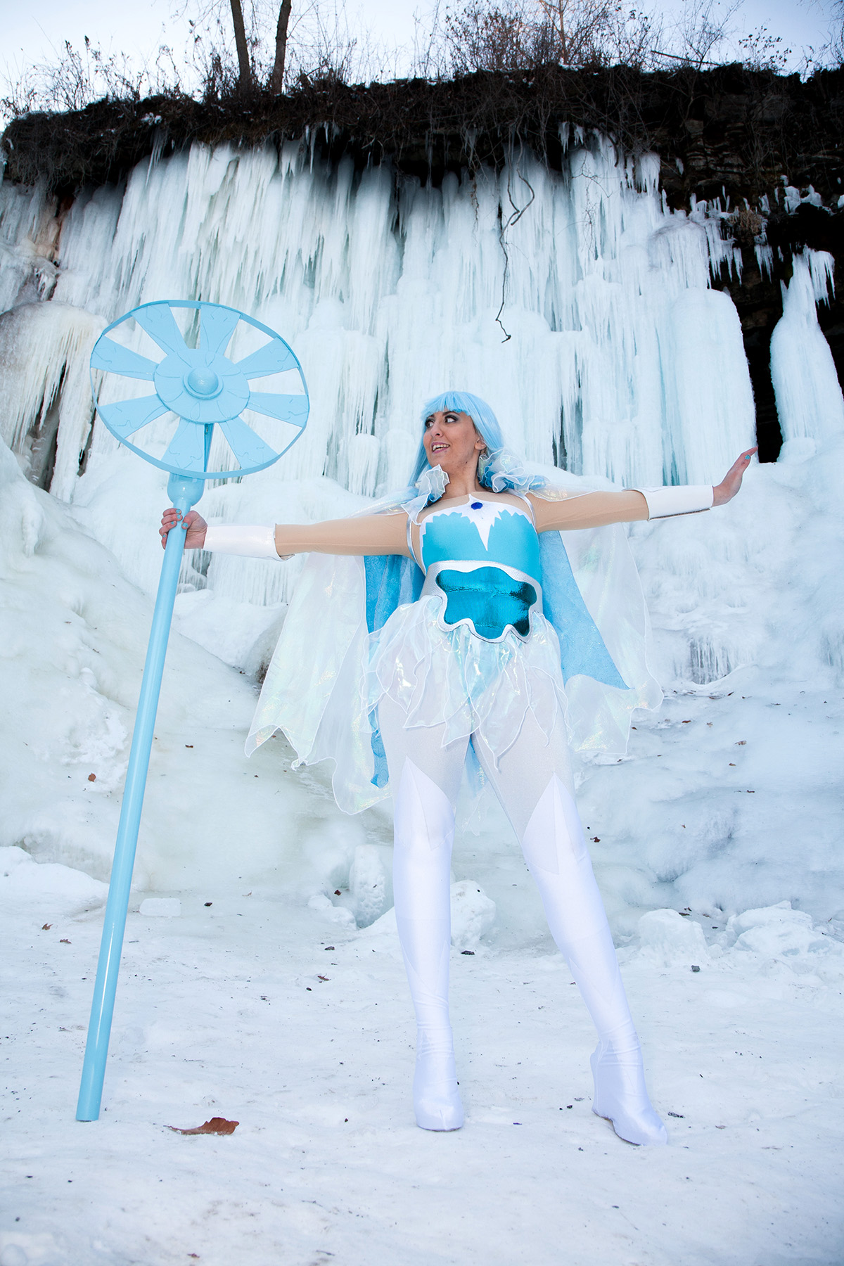 A cosplayer dressed as Frosta from She-Ra. She is pictured in front of a wall of dripping ice.