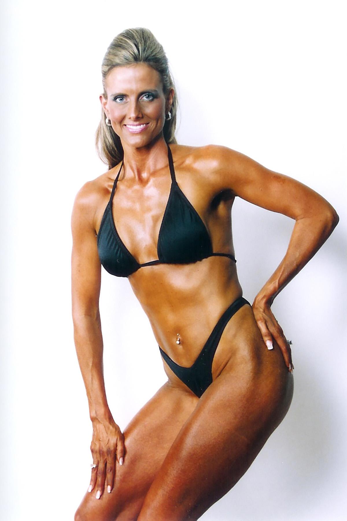 A fitness model posing in a black bikini.