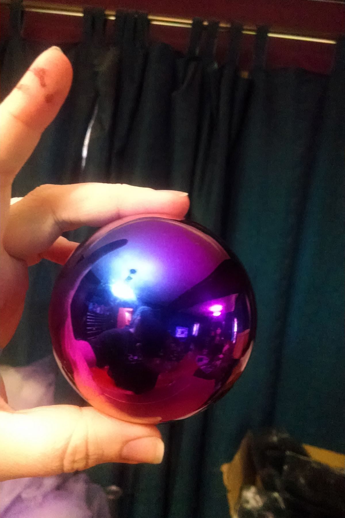 A hand holds up a glass gazing ball. It looks like a brightly coloured oil slick, purple with blues and yellows.