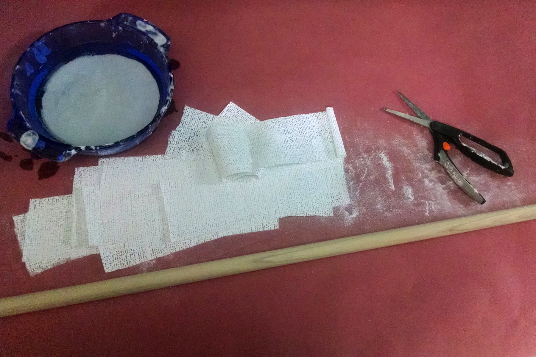 A long, wide dowel, scissors, plaster bandages, and a bowl of water on a work surface lined with pink rosin paper.