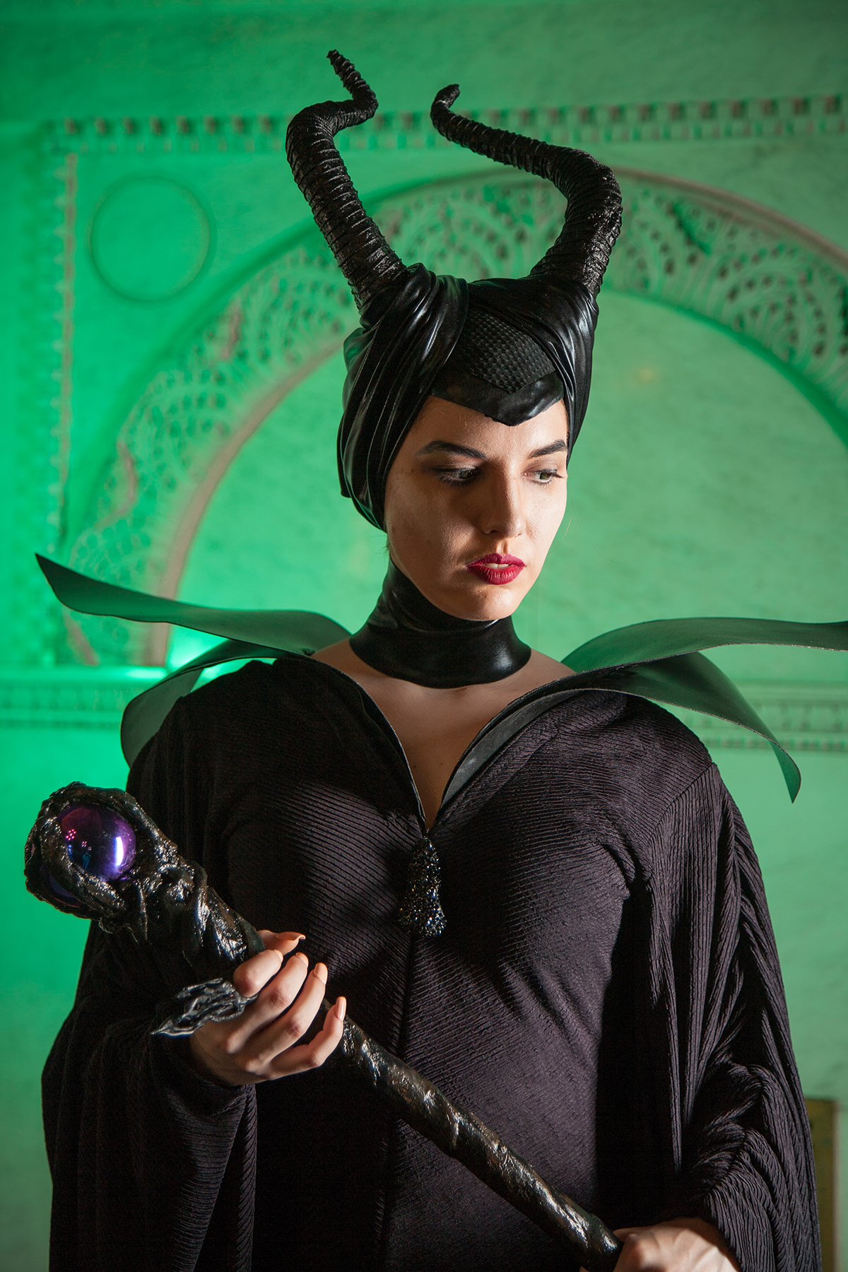 A Maleficent cosplayer, holding her stuff. She is pictured against a green background.