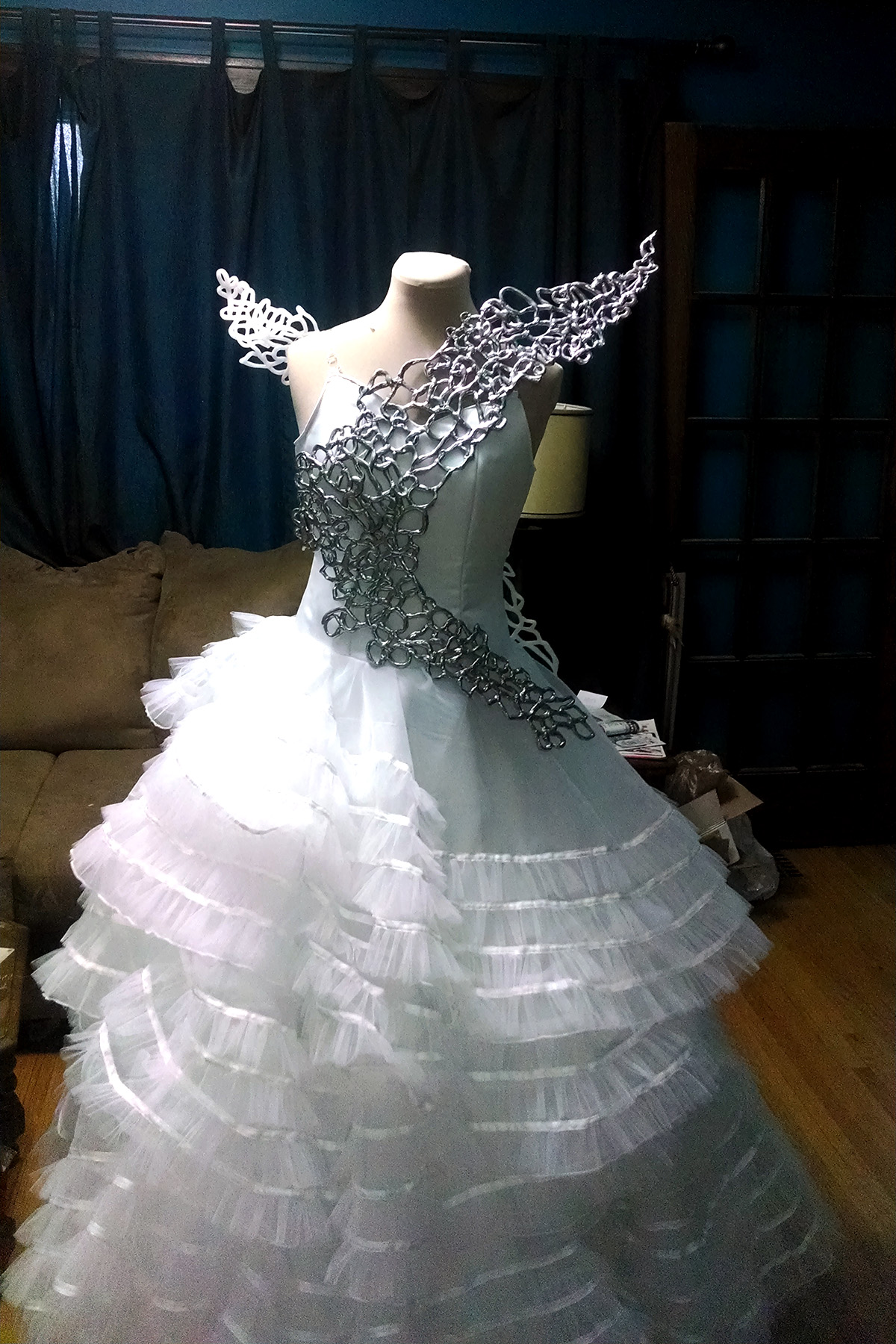 The two Katniss wings attached to the start of the Hunger Games wedding gown, on a dress form - front view.