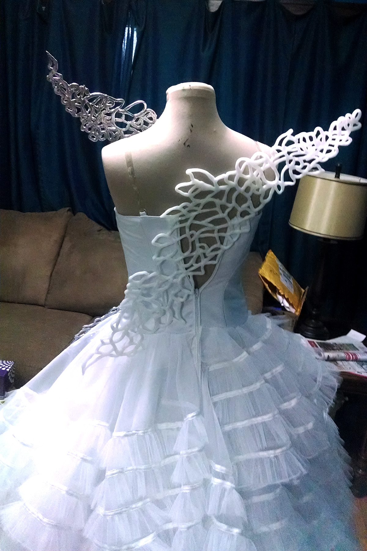 The two Katniss wings attached to the start of the Hunger Games wedding gown, on a dress form - Back view.