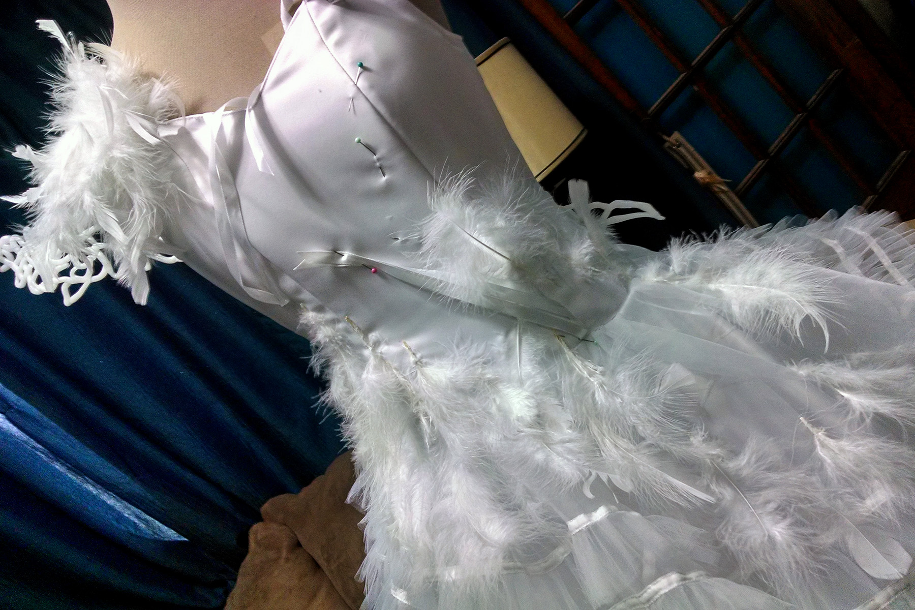 A close up view of the in-progress wedding gown bodice.  There are pieces of white ribbon pinned to a few places on the bodice.