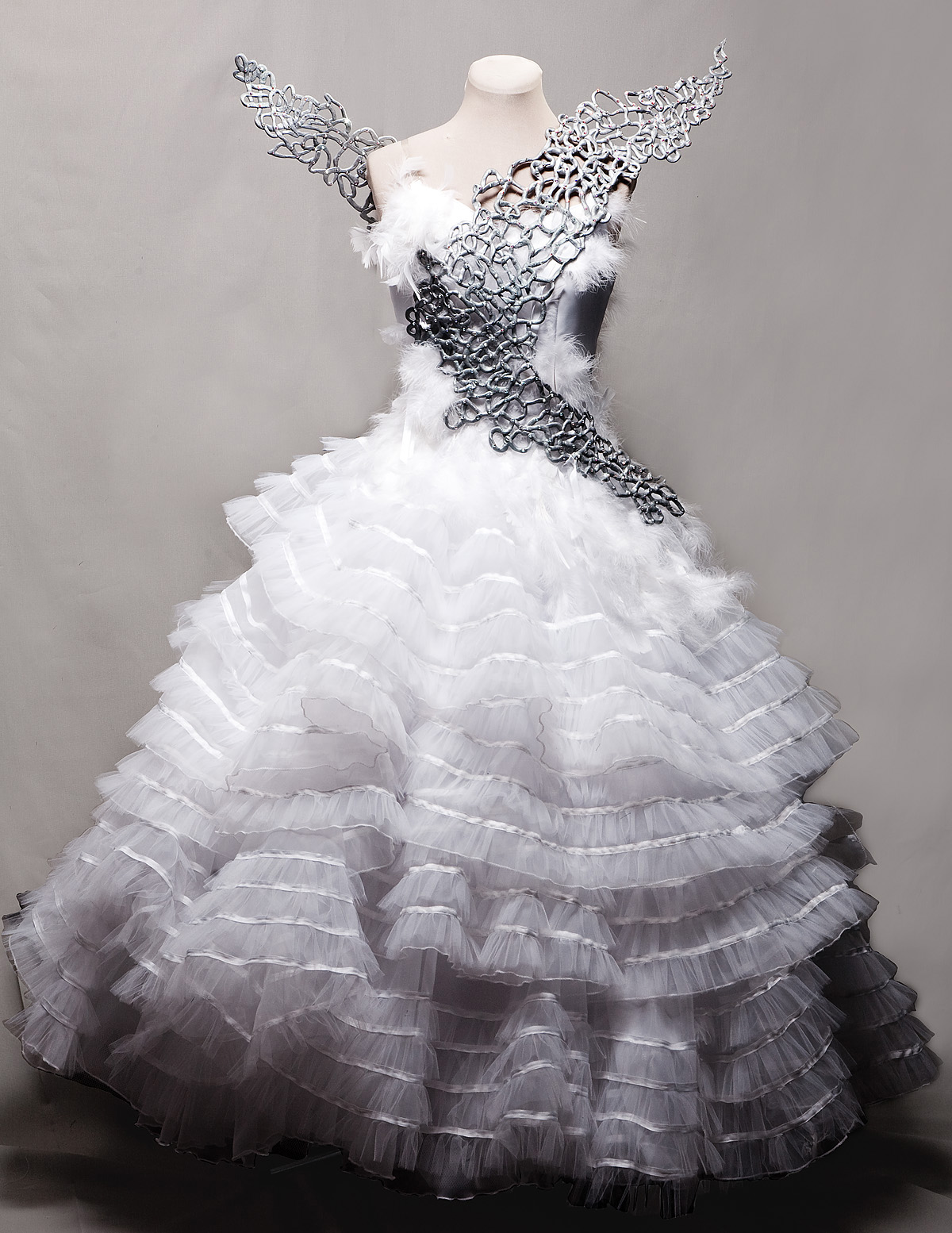 """A replica of Katniss's Wedding Gown from The Hunger Games: Catching Fire.  It has multiple billowy layers of tulle & ribbon, and silver metallic looking filigree """"wings"""" across the front and peeking out from the back."""
