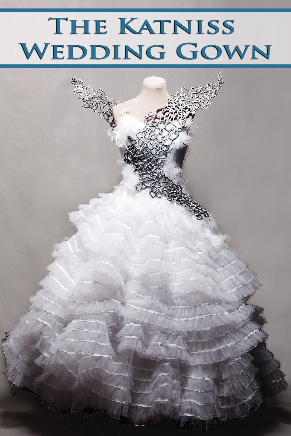 """An elaborate wedding down with silver wings, on a dress form.  Blue text overlay says """"The Katniss Wedding Gown""""."""