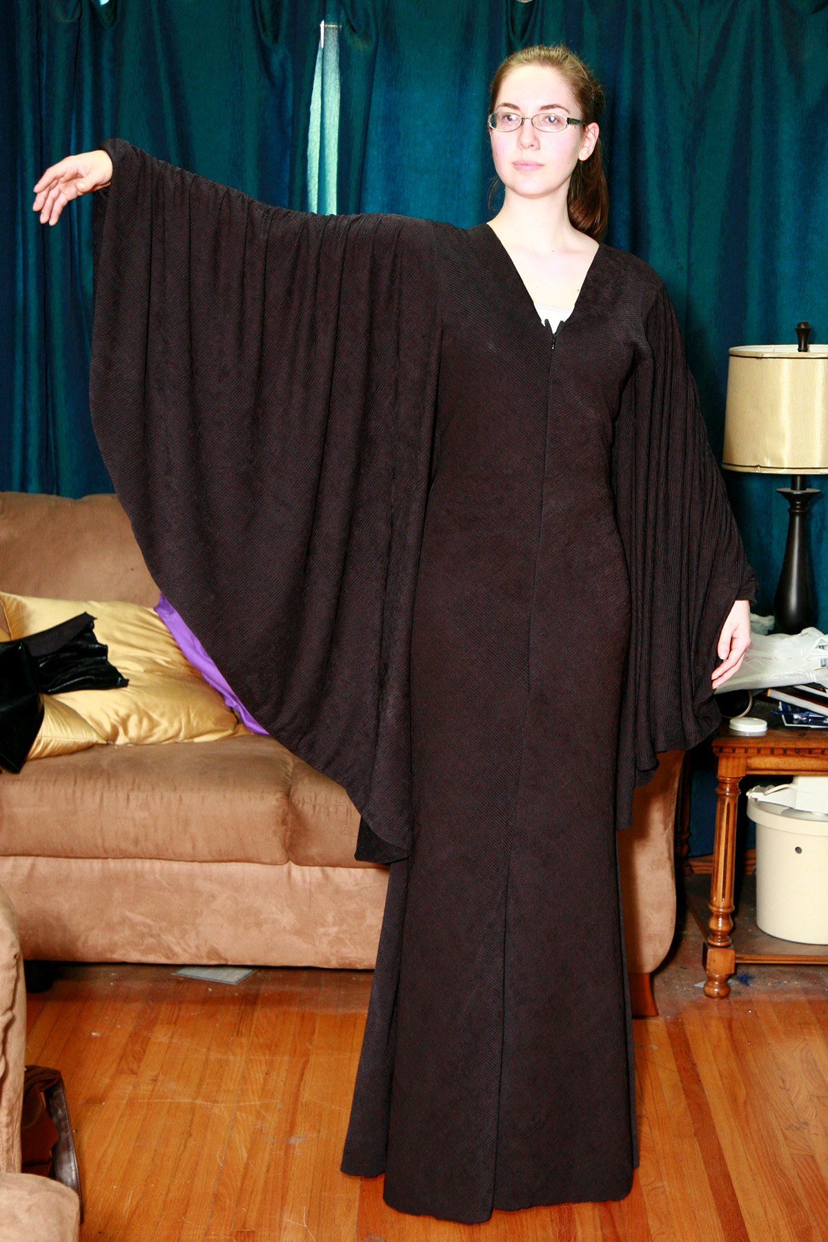 A cosplayer wearing Maleficent's Gown, one arm extending out to the side to show off the batwing sleeve.