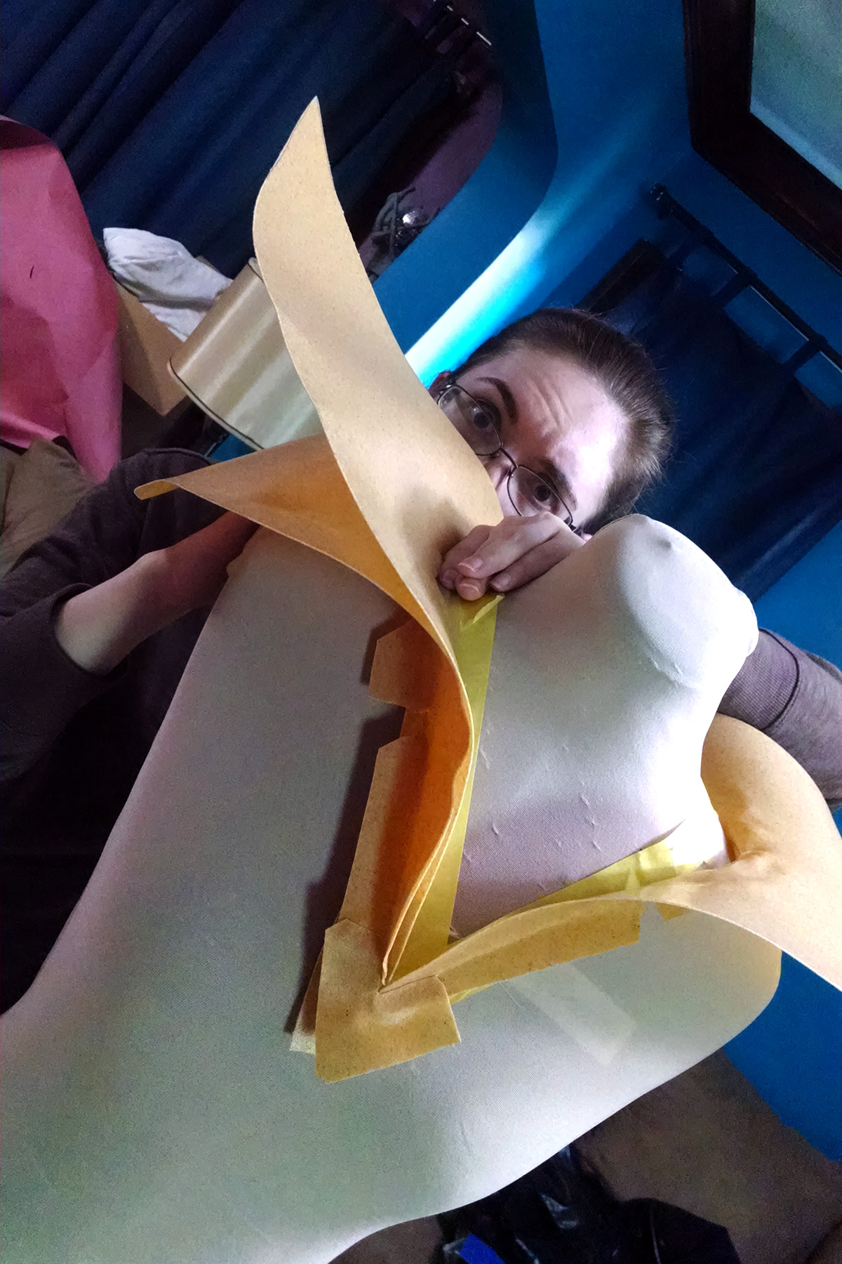 The shoulder wings have been cut and molded from Worbla, a cosplayer peeks out from behind them.