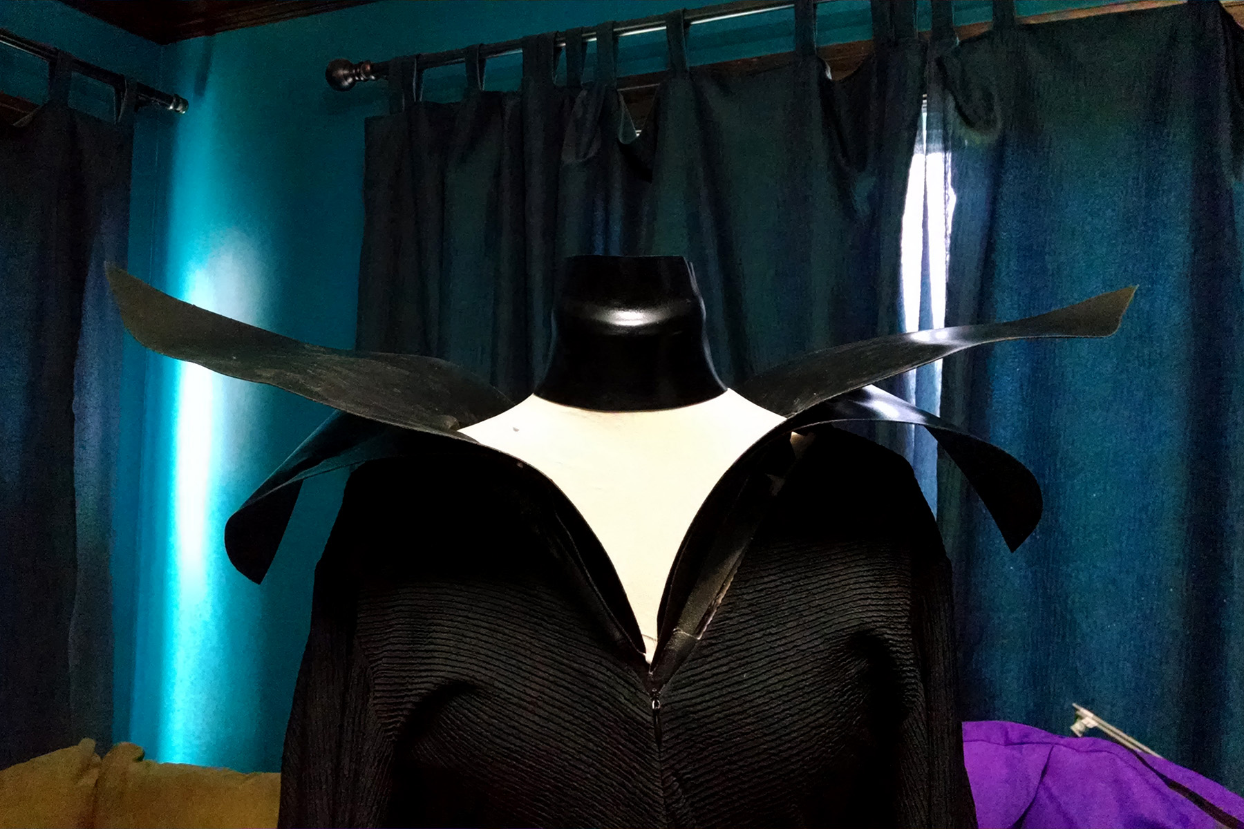 The Collar, Shoulder wings, and gown on a dress form.