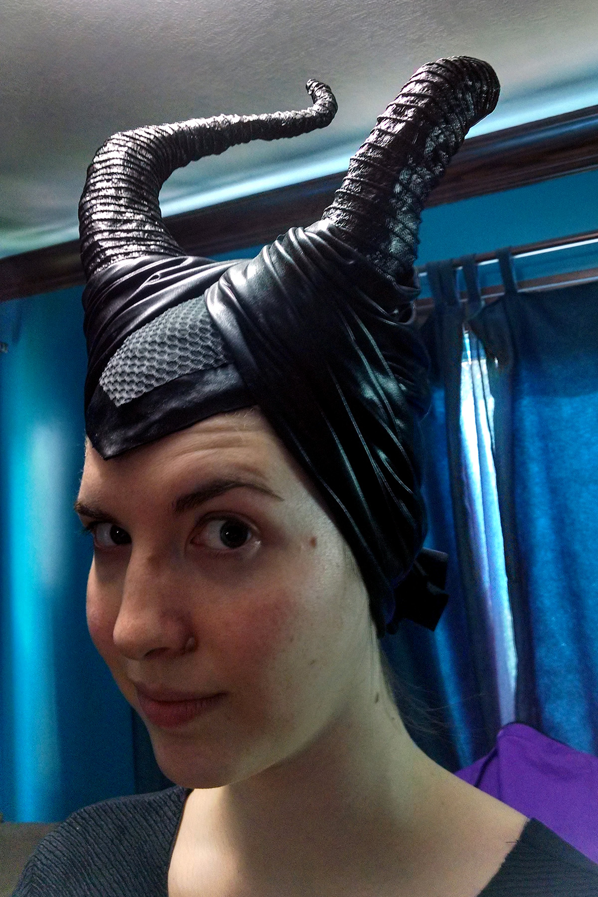 A cosplayer wearing the Maleficent headpiece and horns.