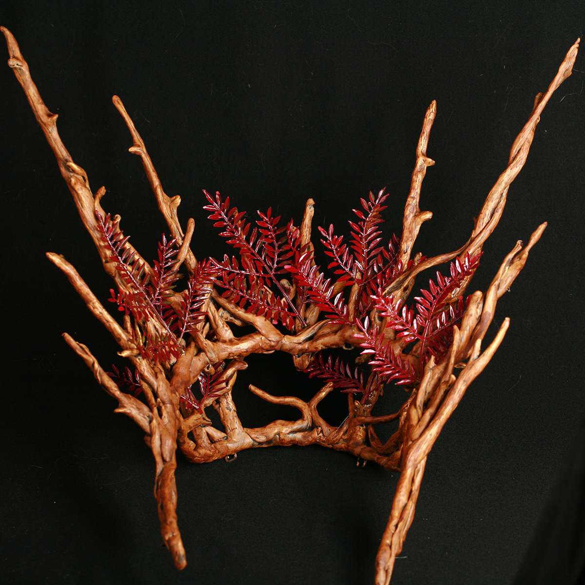 A plastic replica of a Thranduil crown - from The Hobbit -painted to look realistically like wooden twigs. Small branches of red plastic leaves are woven among the branches.
