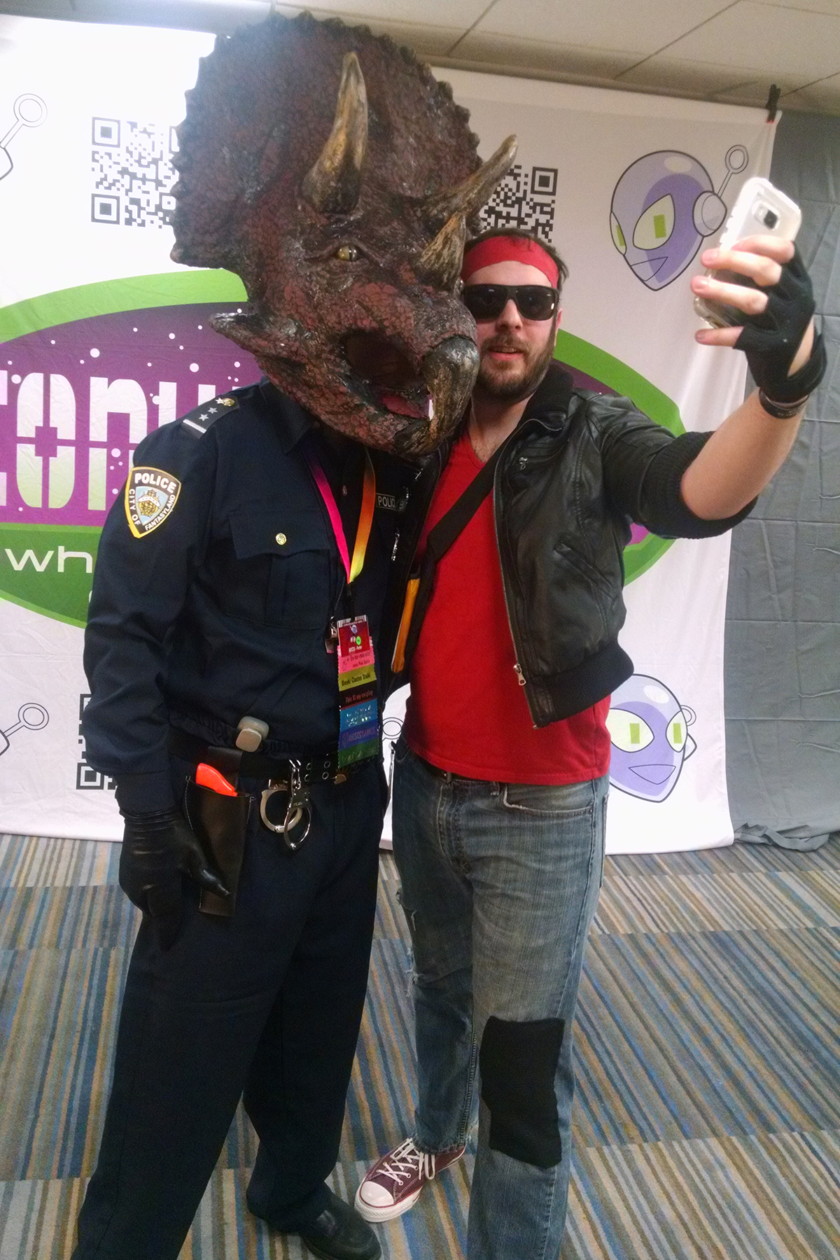 Two cosplayers taking a selfie together. One is dressed as Kung Fury, the other as Triceracop.