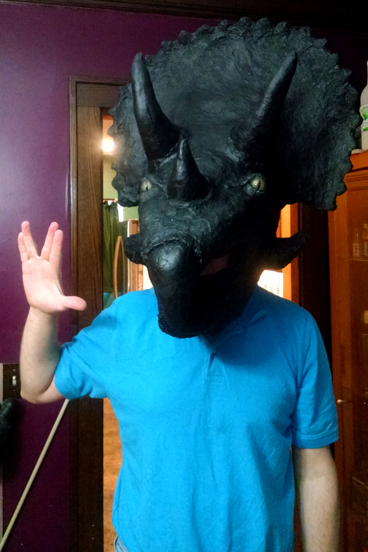 A man wears an all black Triceracop mask while giving the vulcan salute.