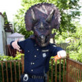 A man in a police uniform and oversized triceratops helmet - Triceracop Cosplay.