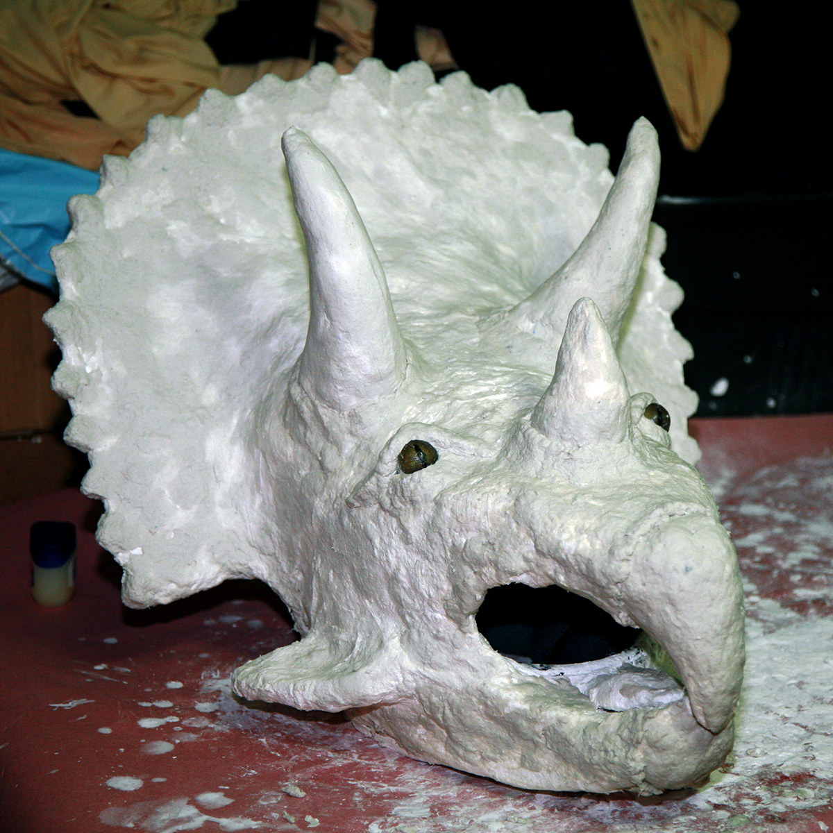 An all white plaster sculped mask of a triceratops dinosaur.