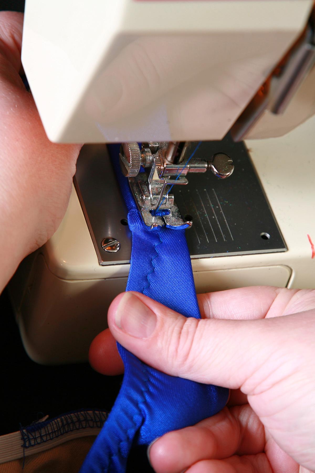 A blue bikini bottom being guided through a sewing machine.