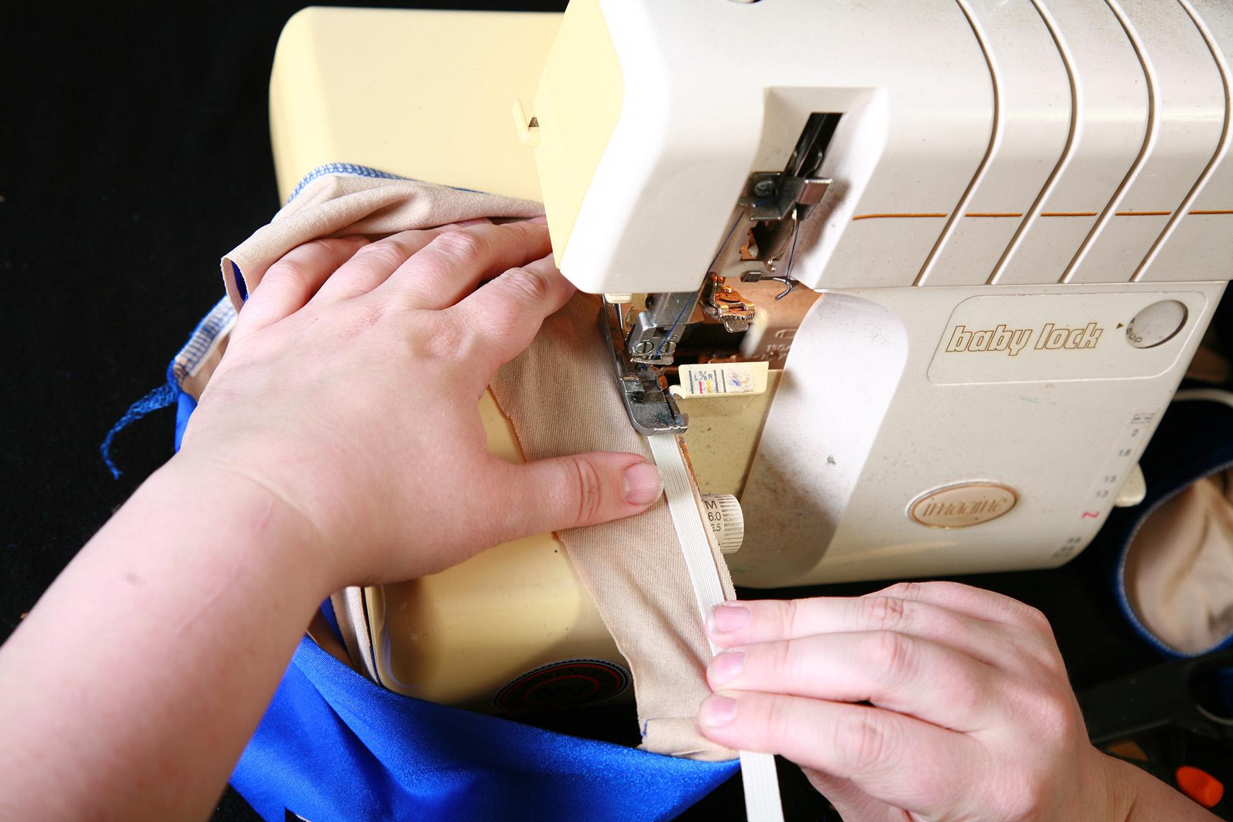 Hands guide a blue, lined bikini bottom through a sewing machine.