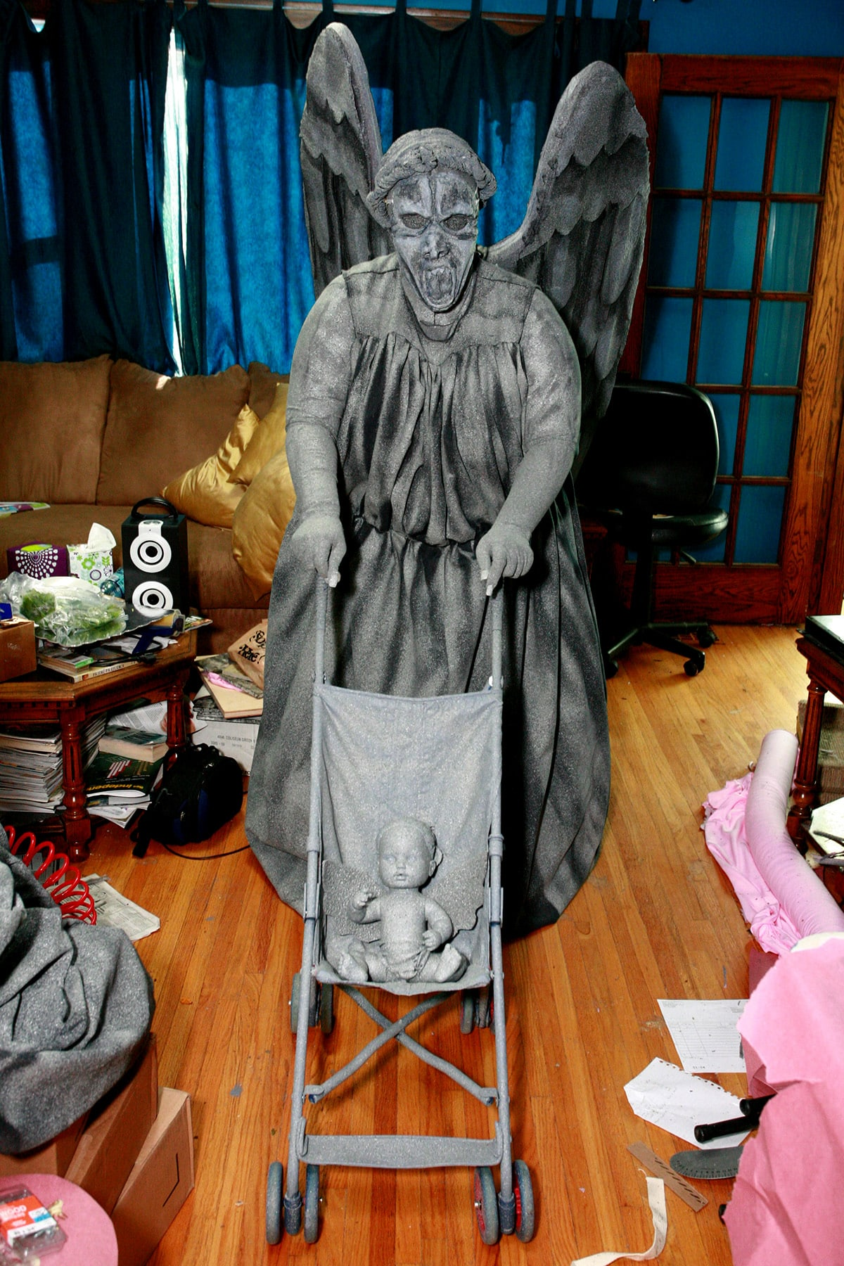 A person dressed as a Weeping Angel, pushing a baby weeping angel in a stroller.