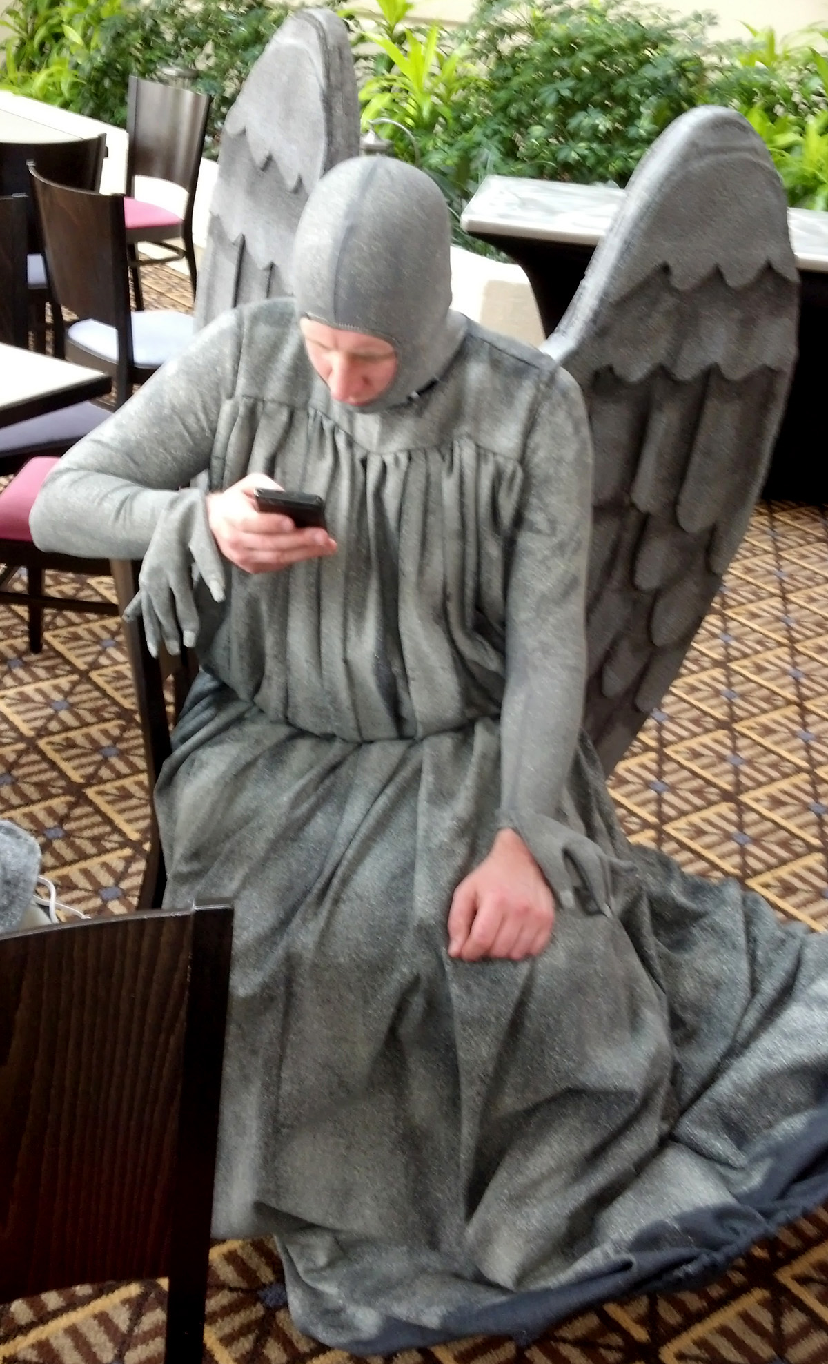 A person dressed as a weeping angel. His mask is off and he is checking a phone.