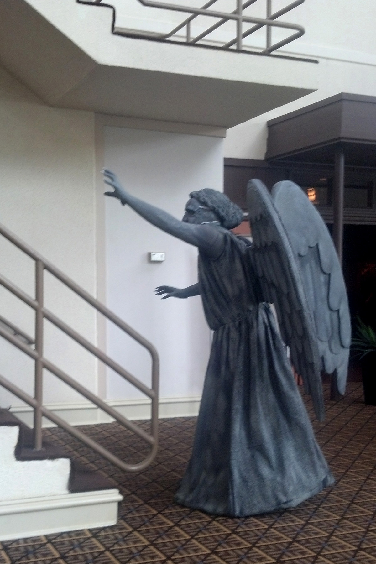 A person dressed as a weeping angel, posing at the bottom of a stair case.