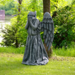 A person dressed as a weeping angel statue in a park.