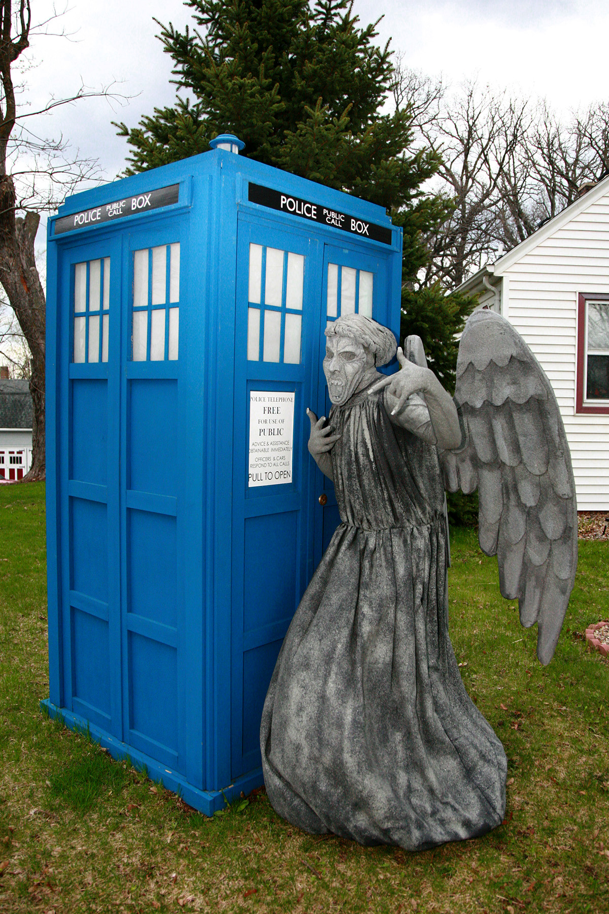 A person dressed as a weeping angel, leaning on a full sized TARDIS.