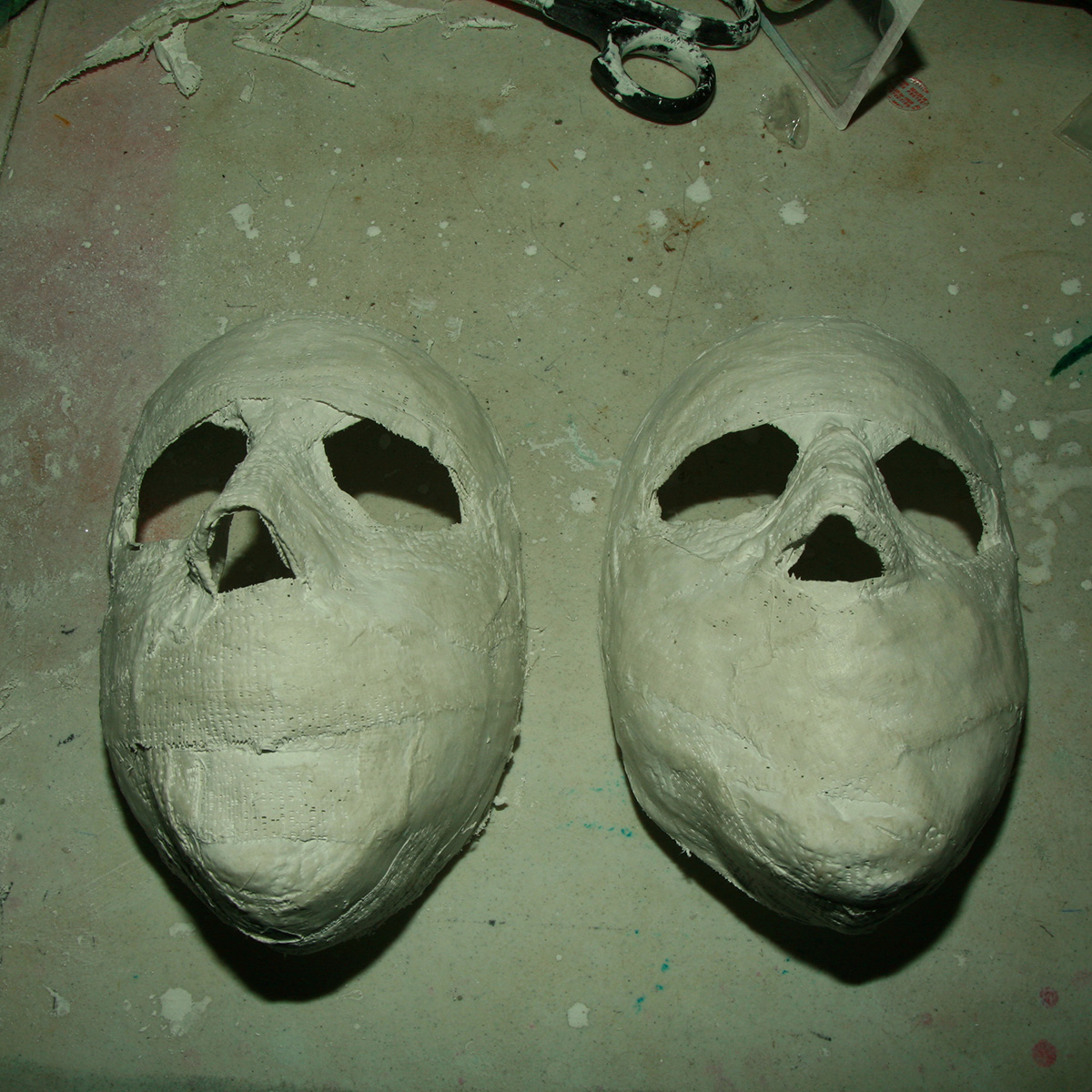 Two very basic plastic face masks on a table.