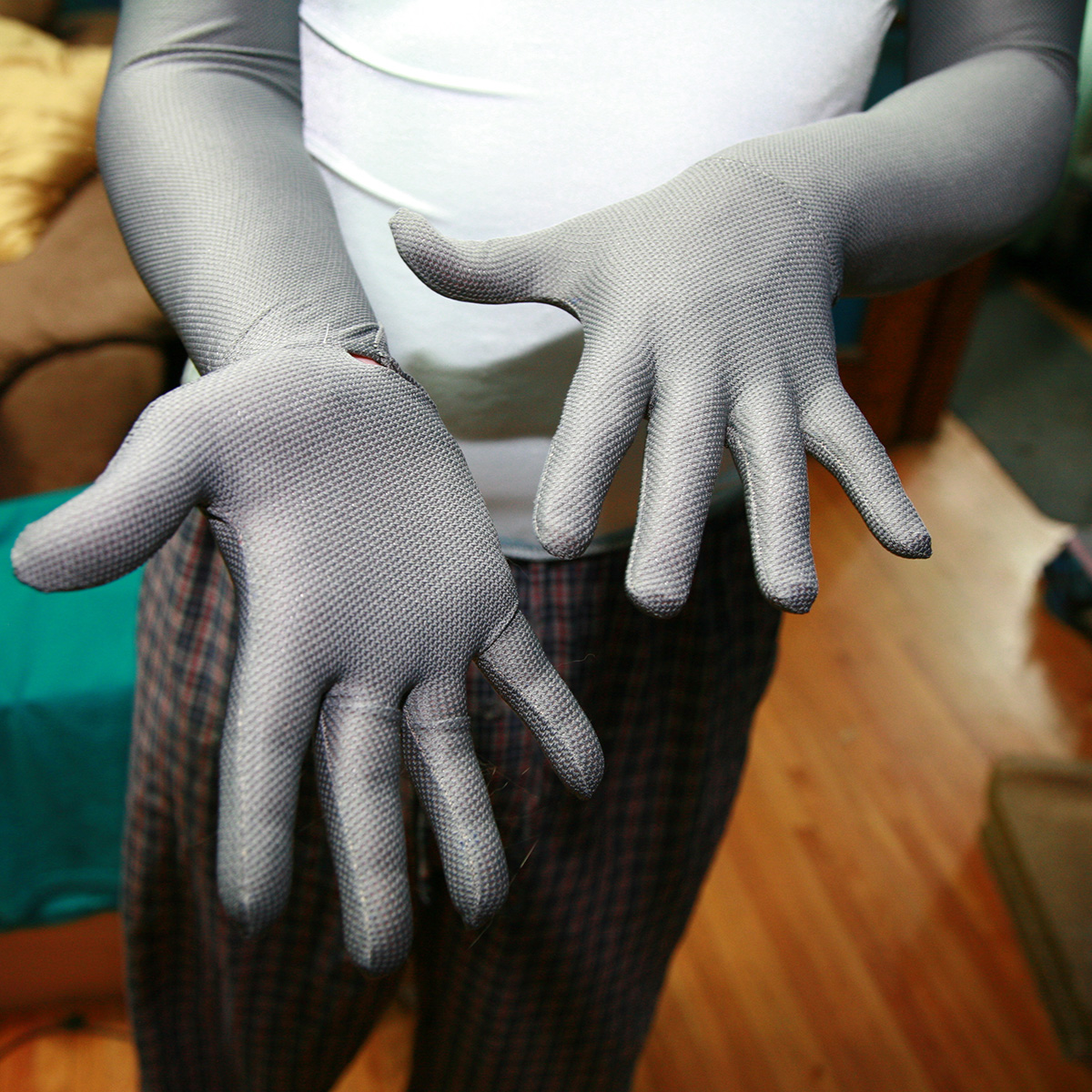 close up view of two hands in long grey gloves.