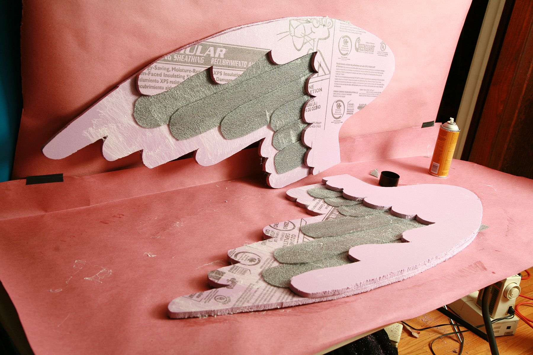 A set of large wings made from pink foam insulation.