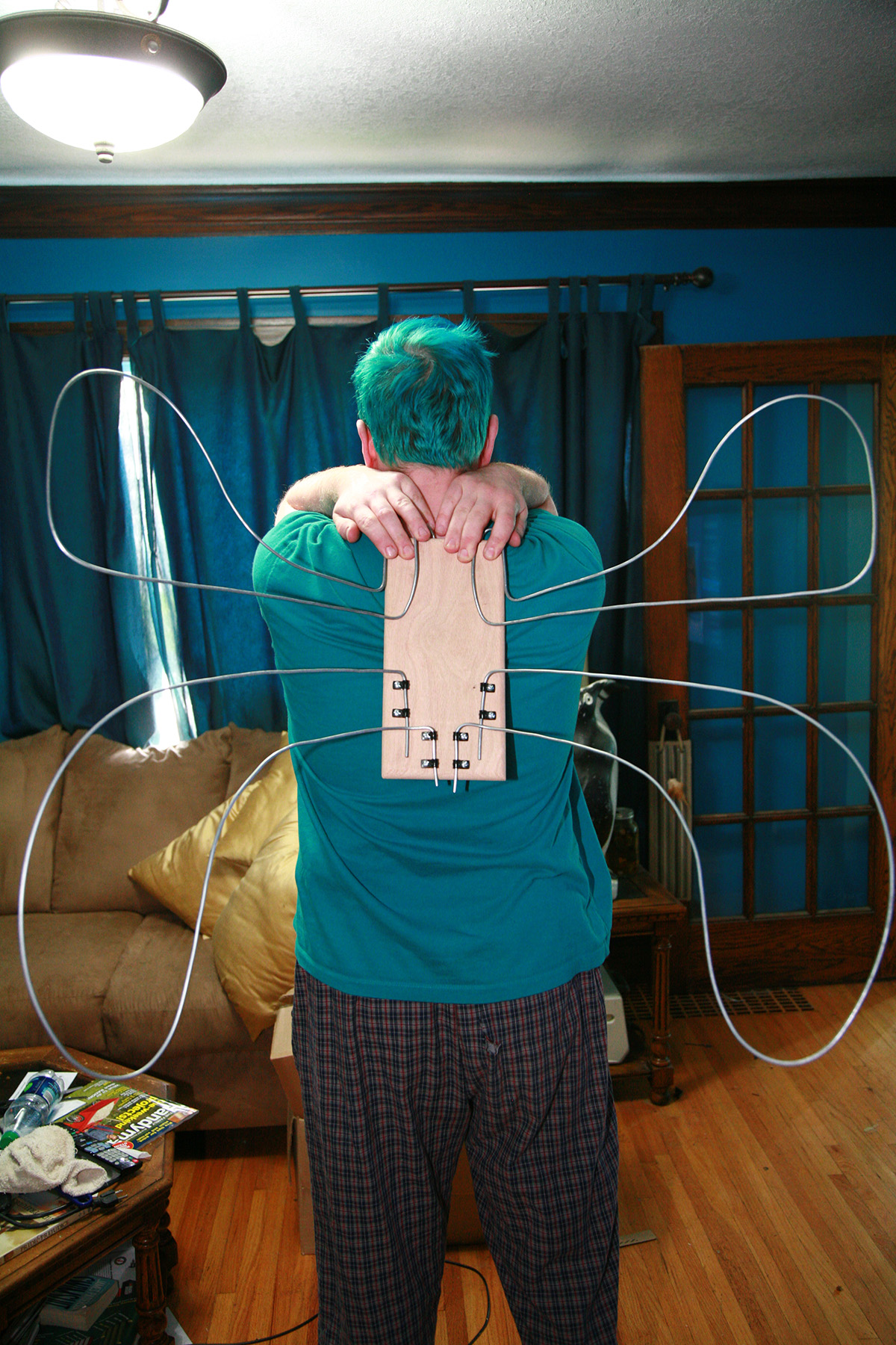 The back of a man holding a rectangle of wood against his upper back. Loops of wire vaguely resemble butterfly wings.